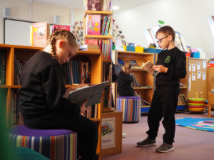 Two young kids reading books in the school library